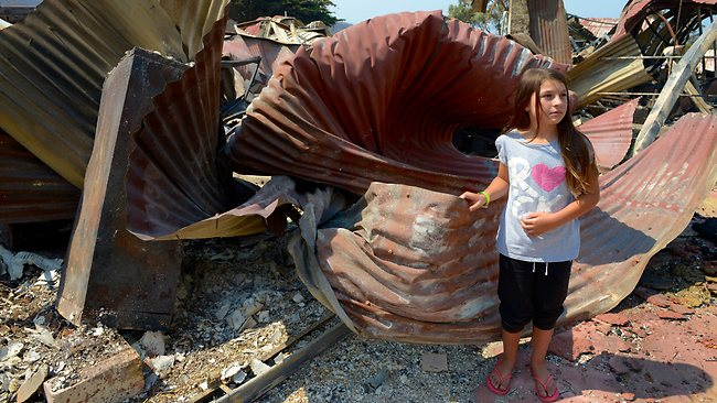 Billie Hasett, 9, visits what is left of her school in Dunally, Tasmania. Picture: Newton Matthew