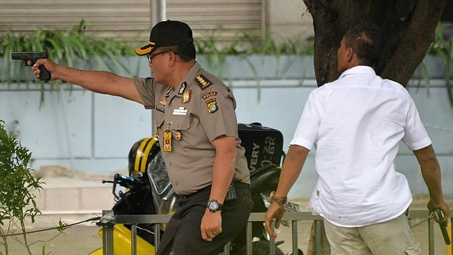 Chaos ... an Indonesian policeman fires his handgun towards suspects outside a cafe after