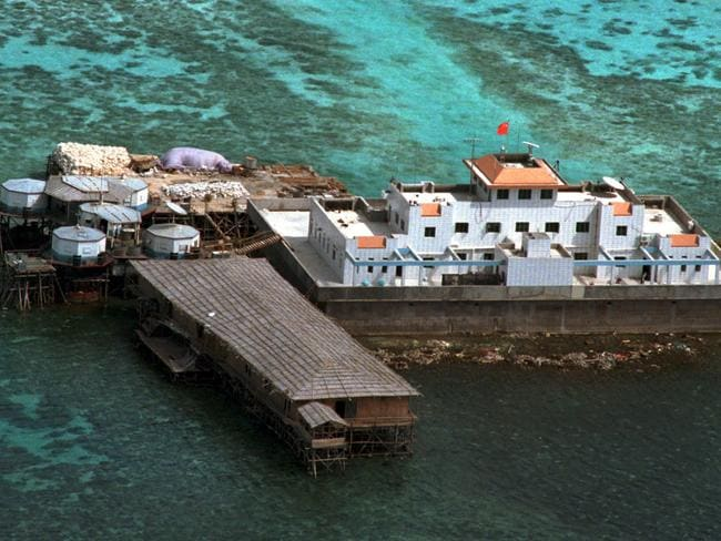 A Chinese flag, red-coloured, flies from concrete structures on the Mischief Reef off the disputed Spratlys group of islands in 1999. Picture: AP Photo/Aaron Favila