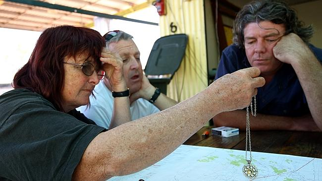 Lorelle Trickett tests out her crystals on the Barrow Creek map with Larry Cook and the Daily Telegraph's Paul ...