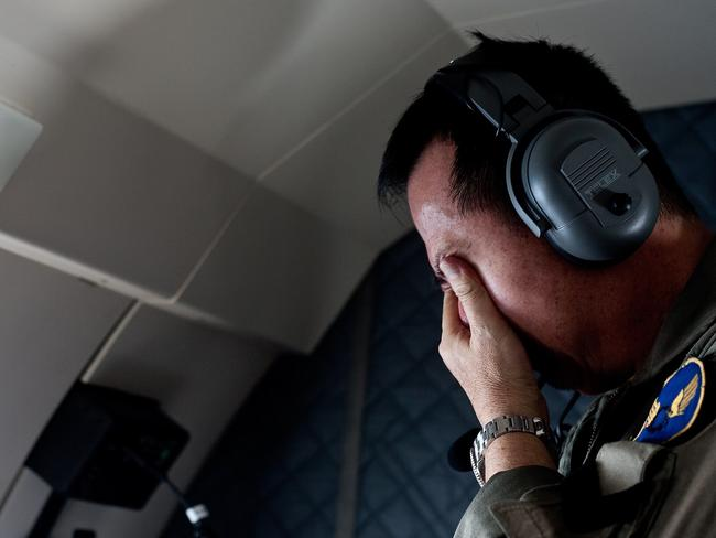 A family member of passengers on-board the missing AirAsia flight QZ8501 reacts after seeing an unidentified floating body during a search and rescue mission with Indonesian military over the Java Sea.