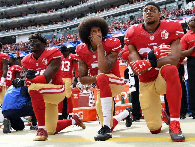 Eli Harold, Colin Kaepernick and Eric Reid of the San Francisco 49ers kneel on the sideline during the anthem prior to the game against the Dallas Cowboys.