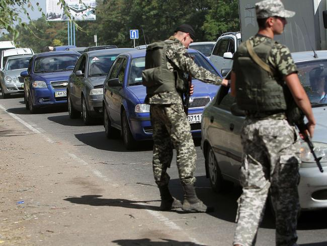 Ukrainian troops stop cars at a checkpoint as people flee Mariupol. Picture: Anatolii Boiko