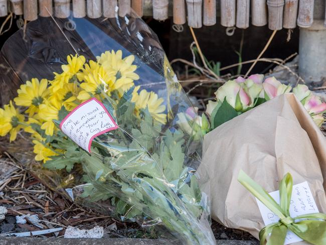 Mourners lay flowers at the murder site. Picture: Jake Nowakowski