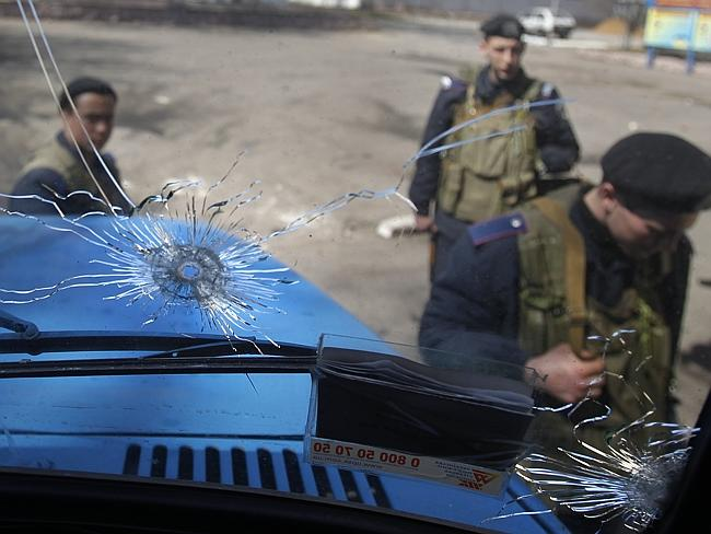 Gunshots...Ukrainian soldiers are seen through the windshield of a military vehicle beari