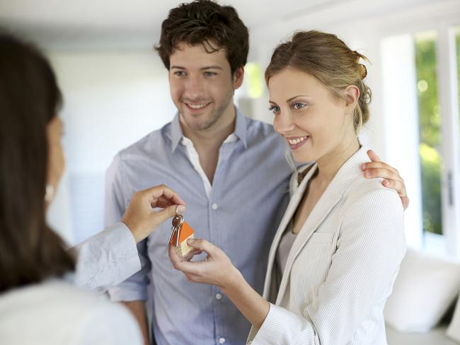 Realising a dream ... Happy young couple getting keys of their new home. Picture: Getty Images