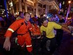 Thai rescue workers carry an injured person from the Erawan Shrine to a waiting ambulance. AFP PHOTO / PORNCHAI KITTIWONGSAKUL