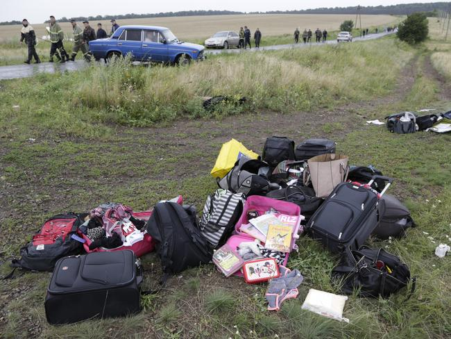 Lost souls ... rescue workers walk past passengers' personal luggage collected at the site of the crashed Malaysia Airlines passenger plane near the village of Hrabove, eastern Ukraine.