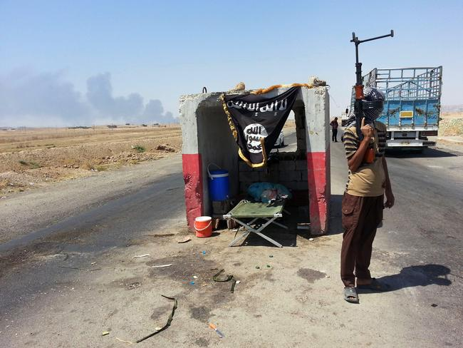Terror threat ... an al-Qaeda-inspired militant stands guard at a checkpoint captured from the Iraqi Army outside Beiji refinery, some 250 kilometres north of Baghdad. Picture: AP