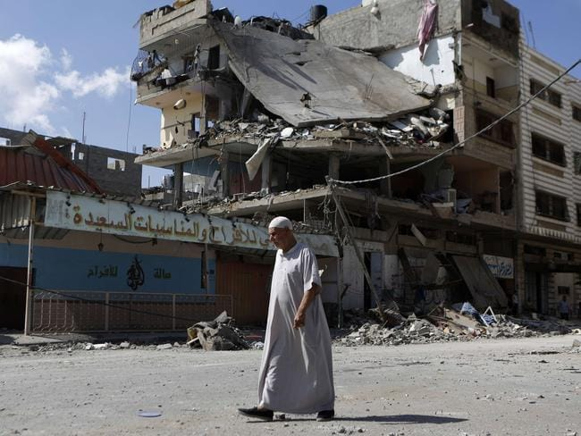 Hours of freedom ... an elderly Palestinian man walks past a heavily damaged building during the temporary five-hour humanitarian ceasefire. Picture: Mohammed Abed