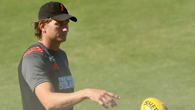 Essendon coach James Hird appears to have the weight of the world on his shoulders as he throws a football in a wheely bin at the end of a training session at Tullamarine onWednesday morning. Picture: Hamish Blair