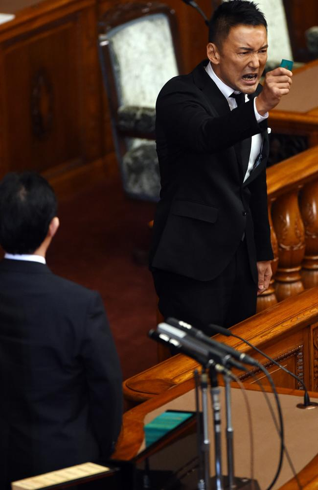 "Opposition party councillor Taro Yamamoto gives the final appeal displaying green-coloured ""No"" ballot prior to his vote for the security bill at the upper house of the parliament. AFP PHOTO / TOSHIFUMI KITAMURA"
