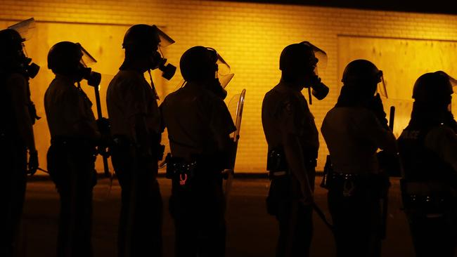 Racial tensions ... police wait to advance after tear gas was used to disperse a crowd during a protest for Michael Brown. Picture: AP Photo/Charlie Riedel