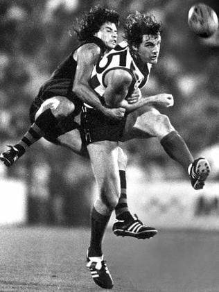 North Melbourne's Donald McDonald gets his kick as Bomber Tony Antrobus tackles.