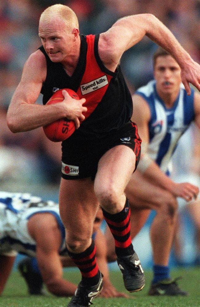 Essendon tough nut Dean Wallis runs away from a pack of North Melbourne players.