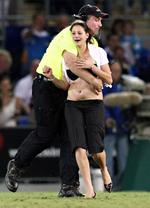 <p>A woman gets grabbed by security early into her attempted streak at a Gold Coast Titans game at Skilled Park, Robina. Pic: Adam Head</p>