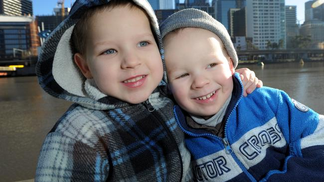 Brothers Jos, 4, and Eli, 3, of Geelong, brace against the cold this morning. Picture: Andrew Henshaw