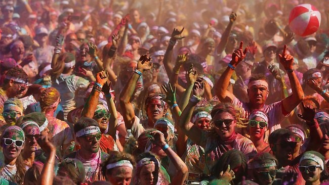 Competitors enjoy a DJ set and throw packets of coloured powder after finishing the Colour Run at Sydney Olympic Park. picture: Getty