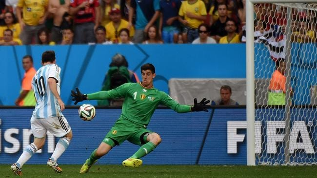 Belgium's goalkeeper Thibaut Courtois (R) prepares to block a shot.
