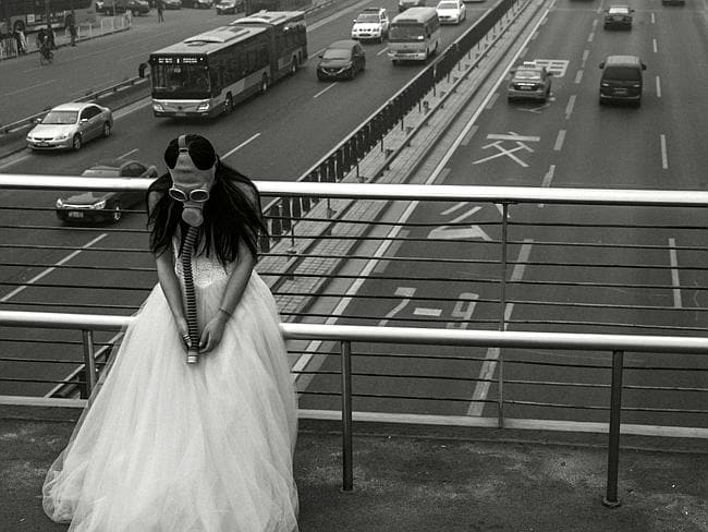 Traffic stopper ... The bride stands above a freeway in the Chinese capital. Many roads have been shut due to the thick smog. Picture: Austral. Source: Supplied