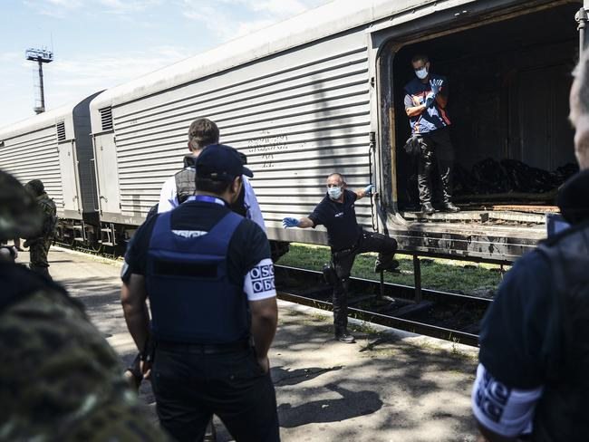 Monitors from the Organization for Security and Cooperation in Europe (OSCE) and members of a forensic team inspect a refrigerator wagon containing the remains of victims from Flight MH17