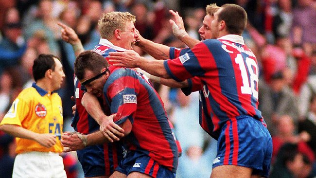 Darren Albert is congratulated by Adam Muir (headband), Lee Jackson (18) and Scott Conley after scoring winning try during 1997 Newcastle v Manly ARL grand final at SFS in Sydney. Picture: Andrew Darby