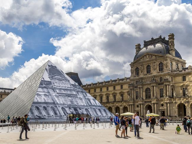 Paris, France - June 17, 2016: A daytime HDR shot of the Lourve in Paris. The Lourve is visited by thousands of tourists every year and you can see some of them roaming the grounds in this photo.