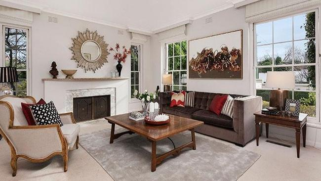 The formal lounge and dining room has an open fireplace at 150 Kooyong Rd, Toorak.