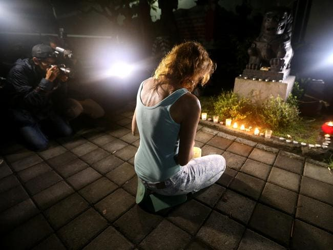 Vigil ... A woman prays and lights candles at the jail. Picture: Adam Taylor