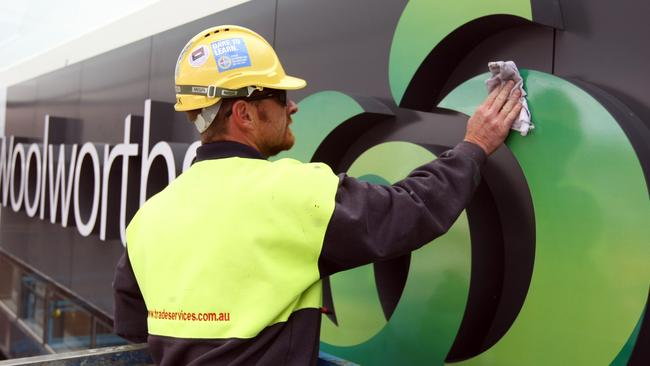 Mick Mahony, of Trade Services, polishes the new Woolworths sign on the new store at Chadstone shopping centre. This is the first rebranding of Safeway to Woolworths to happen.