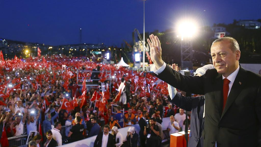 Turkey's President Recep Tayyip Erdogan waves to his supporters as he arrives to commemorate the one year anniversary of the failed coup. Picture: AP