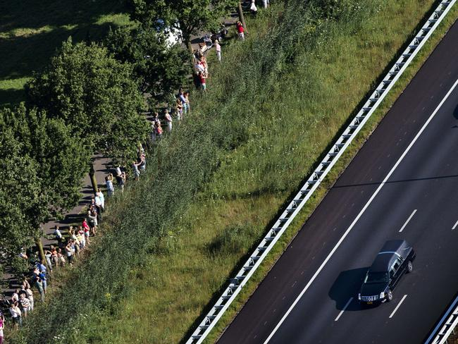 Procession ... people stand on the side of the road as a convoy of hearses carrying the bodies of victims of the downed Malaysia Airlines flight MH17 moves to Hilversum where the bodies will be examined.