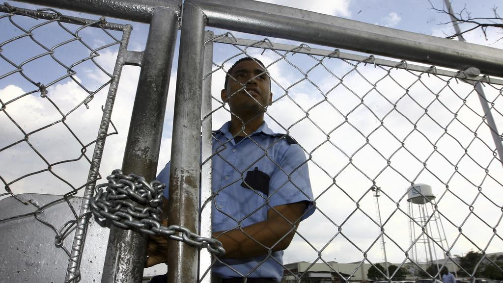 A security guard stands behind a fence at the General Motors assembly plant in Valencia, Venezuela. GM says it has halted operations in Venezuela after authorities seized its factory. Picture: Juan Carlos Hernandez/AP