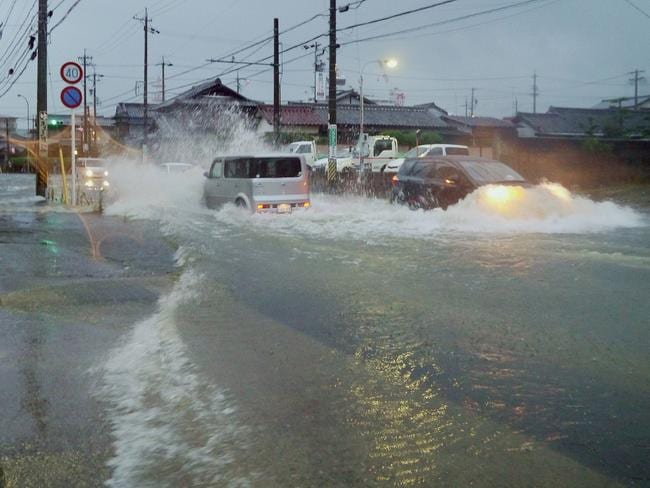 Deluge drivers ... Vehicles drive down a flooded road in the city of Tsu, Mie prefecture as Typhoon Halong brings heavy rain. Source: AFP