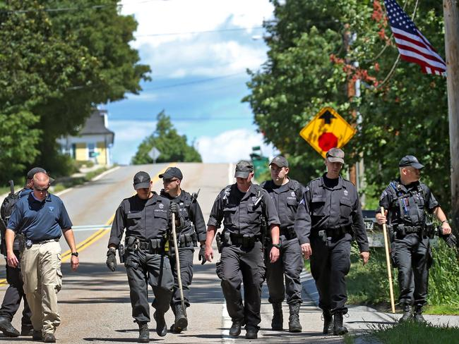 State Police walk down the street in Princeton, Massachusetts, after combing the woods for clues to Ms Marcotte's killer. Picture: David L. Ryan/The Boston Globe via AP