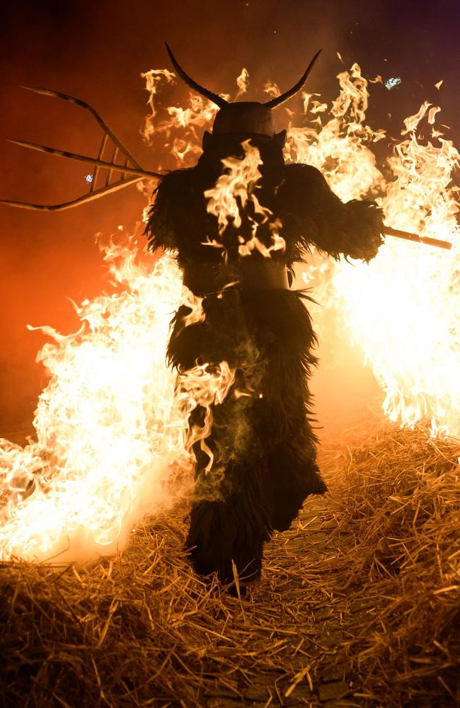 A participant dressed as a 'Krampus' creature walks through fire during 'The Hike of the Krampus of Three Lands' in Podkoren, Slovenia. Picture: AFP