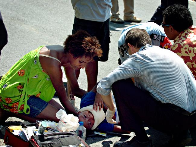 Hit and run incident ... Serah Kevin is treated by a medic and a woman believed to be her mother. Picture: Post-Courier