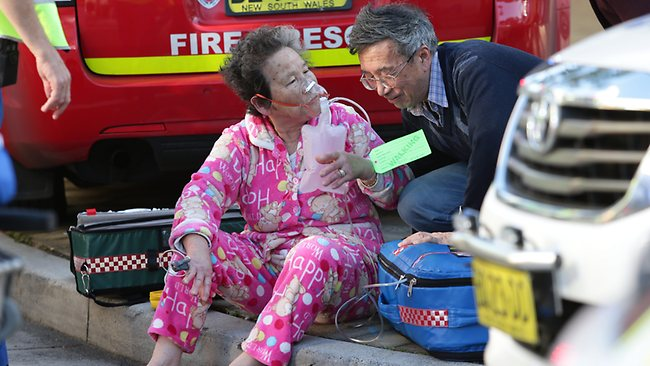 An elderly woman evacuated from the building receives medical attention. Picture: Bill Hearne