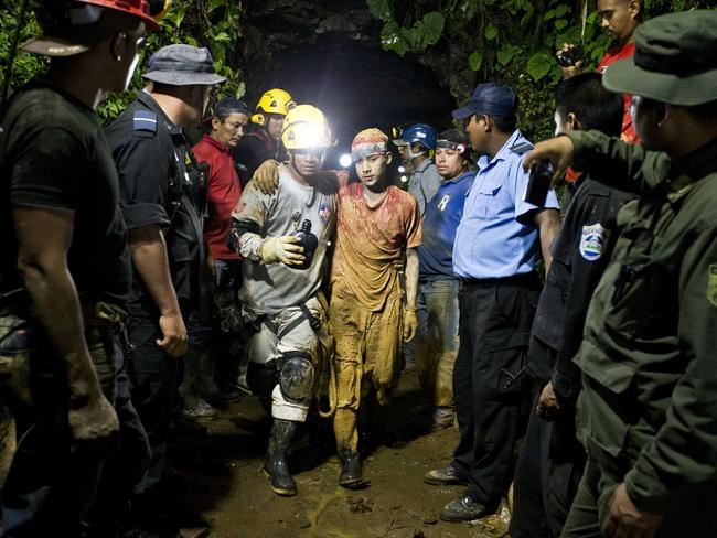 Freedom at last ... young miner Leber Vivas Gonzales, 16, centre right, walks with his arm over the shoulders of a rescue worker.