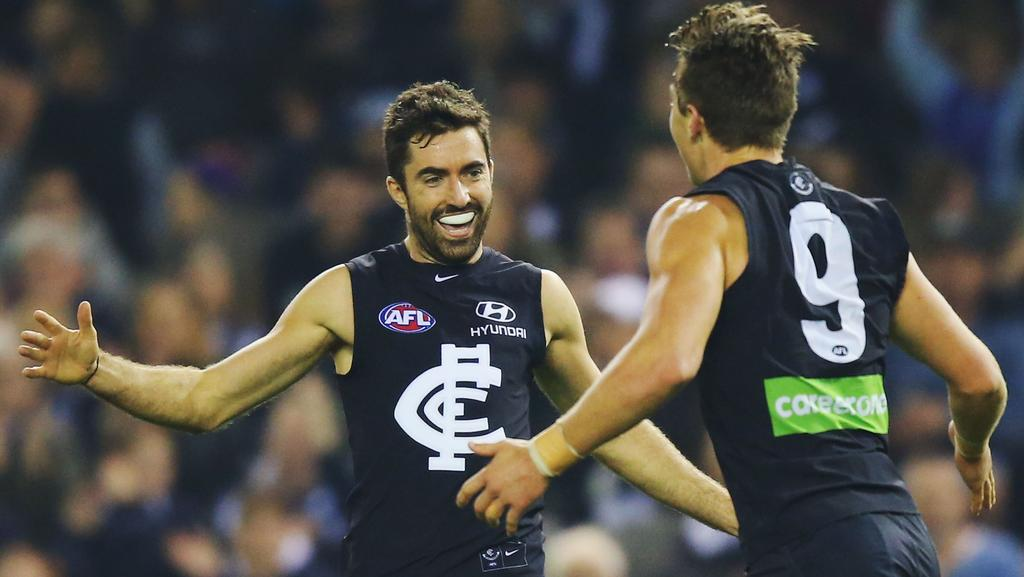 Patrick Cripps of the Blues (R) celebrates a goal with Kade Simpson.