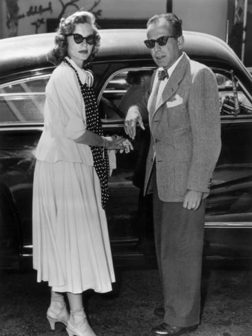 Circa 1945: Full-length image of married American actors Lauren Bacall and Humphrey Bogart standing by their car. Picture: Supplied