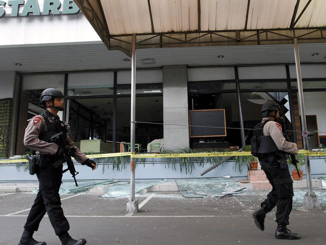 Indonesian police officers walks past debris at the scene of a bomb blast at a Starbucks Coffee store in Jakarta in January 2016. Picture: AAP