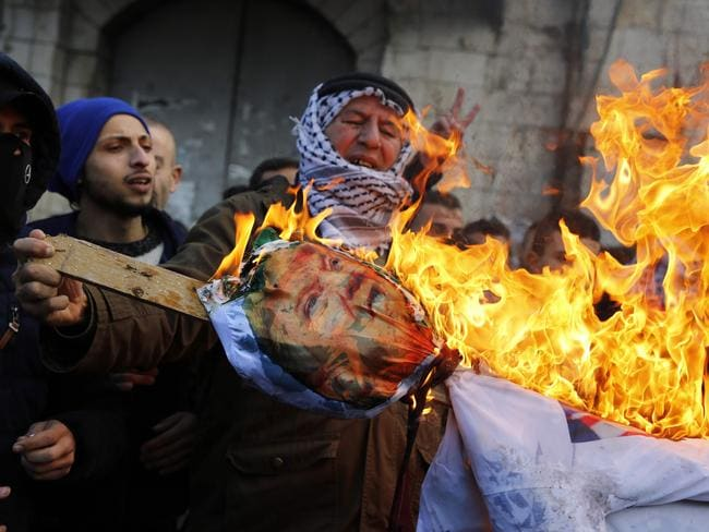 Palestinian protesters burn an effigy of US President Donald Trump in the West Bank city of Nablus. Picture: AFP PHOTO / Jaafar ASHTIYEH
