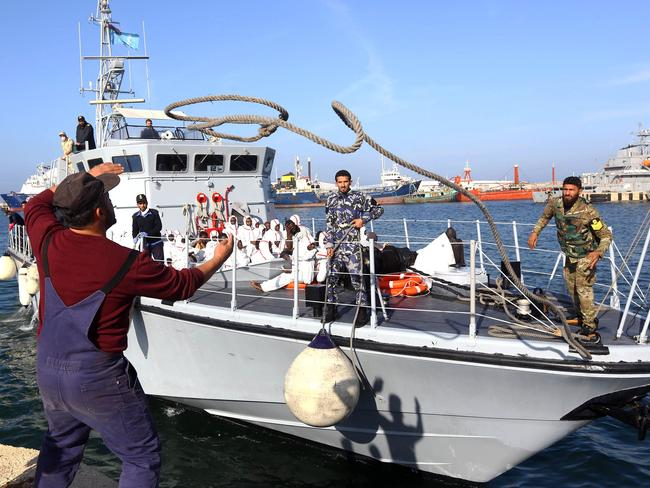 A Libyan aid worker helps dock a ship carrying African migrants at a naval base in Tripoli. Picture: AFP