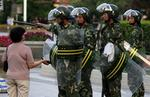 <p>Chinese soldiers tell a woman to move on as they enforce a curfew in Urumqi. Picture: Reuters</p>