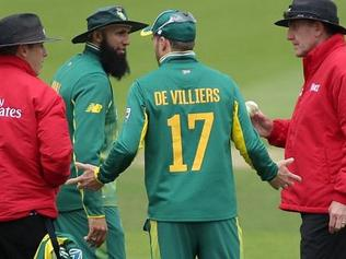 South Africa skipper AB de Villiers hasa word with a the two umpires.