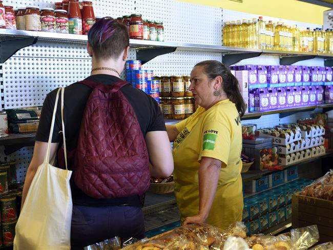 A volunteer helps a customer at OzHarvest Market, a recycled food supermarket, in Sydney. Picture: Saeed Khan