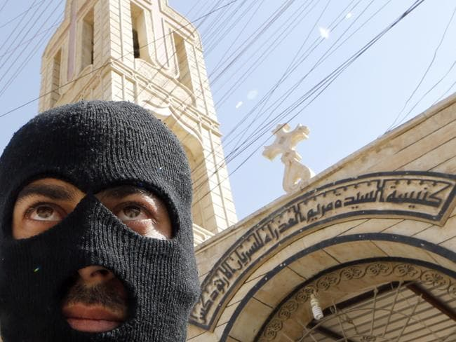 On guard ... An Iraqi security officer, stands guard outside the Church of the Virgin Mary in the northern town of Bartala.