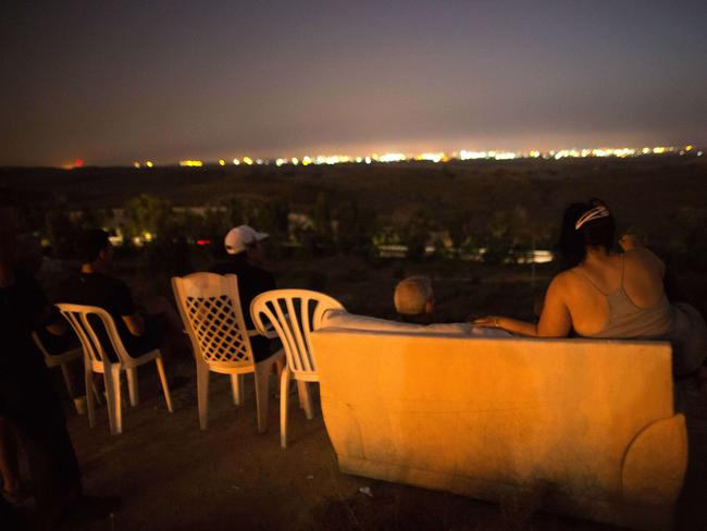 Fireworks show ... Israeli residents, mostly from the southern Israeli city of Sderot, sit on a hill overlooking attacks on the Gaza strip.