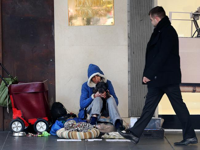 A homeless woman with her dog and possessions, outside David Jones in Melbourne.